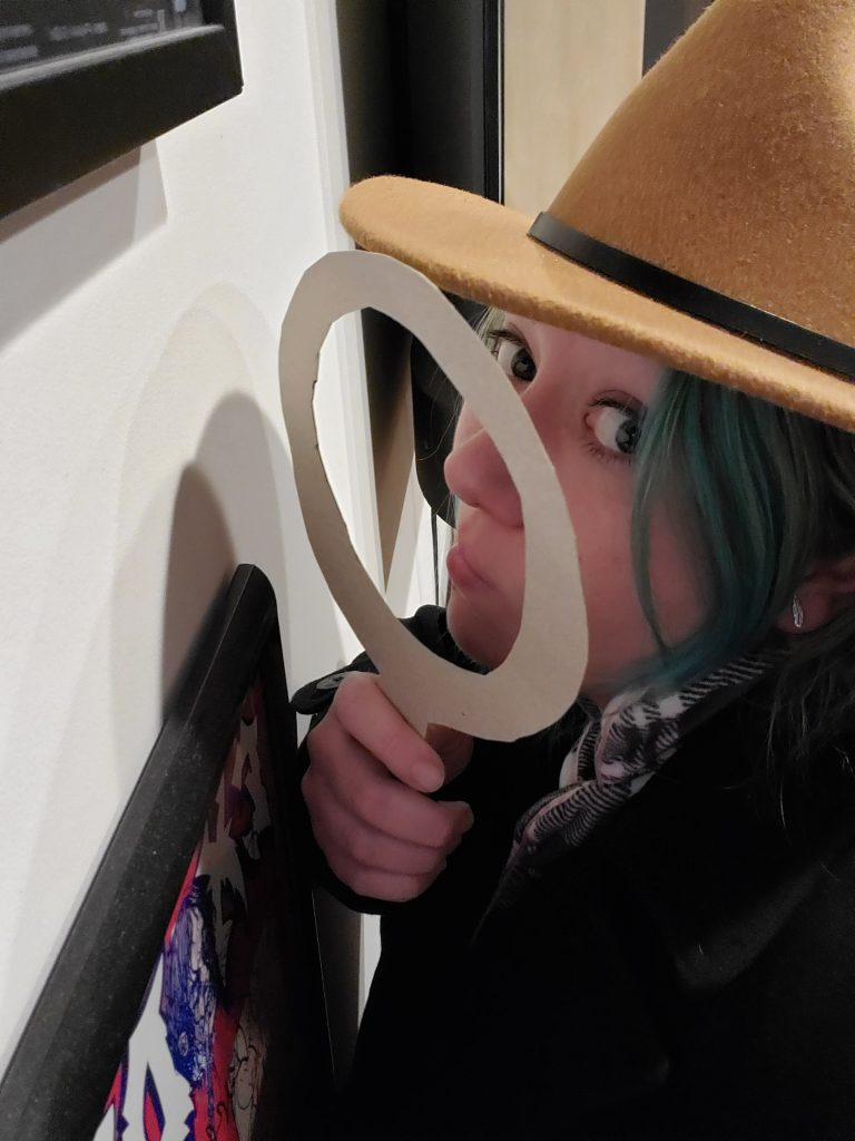 Lindsey holds a magnifying glass to inspect the news.