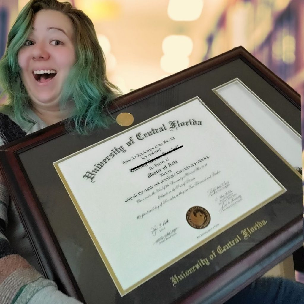 Lindsey is holding up her Master's of Arts degree in history. It covers most of her body. She is smiling and has green hair and a grey sweater.